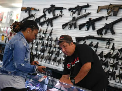 Kiley Russell (L) speaks to salesman Jason Zielinski as she she gets information about buying a gun before taking her concealed carry certification test at the Eagle Sports gun range in Oak Forest, Illinois, July 16, 2017. / AFP PHOTO / JIM YOUNG / With AFP Story by Nova SAFO: …