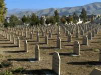 In this Dec. 7, 2006 file photo, men stand at a graveyard where the dead of 1988 gas attack on Halabja, Iraq, by Saddam Hussein's regime were laid to rest. Donald Trump gives credit where credit isn't due when he brands Saddam Hussein a potent foil of terrorists. Iraq's dictator was responsible for gassing thousands of Kurdish civilians, using chemical weapons against Iran, invading Kuwait, crushing political dissent and giving money to the families of Palestinian suicide bombers who terrorized Israelis. (AP Photo/Yahya Ahmed, File)