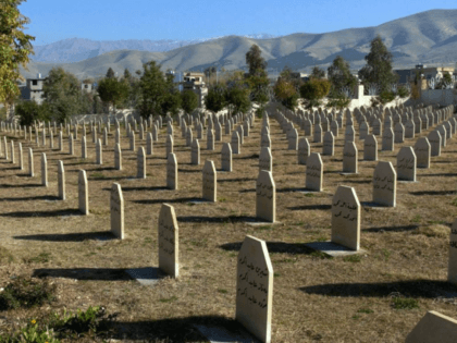 In this Dec. 7, 2006 file photo, men stand at a graveyard where the dead of 1988 gas attack on Halabja, Iraq, by Saddam Hussein's regime were laid to rest. Donald Trump gives credit where credit isn't due when he brands Saddam Hussein a potent foil of terrorists. Iraq's dictator …