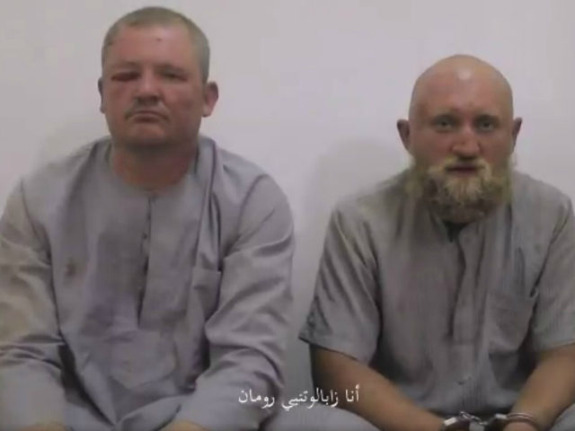 "A man identifies himself as ""Zabolotny Roman"" (R) and his companion as ""Tsurkanov Gregory"" (L), two Russian soldiers allegedly captured by the Islamic State militant group (ISIS) in the eastern Syrian city of Deir Ezzor in this video credited to ISIS's Amaq news agency. Russia previously denied any of its …"