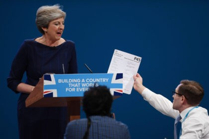 MANCHESTER, ENGLAND - OCTOBER 04: Comedian Simon Brodkin, aka prankster Lee Nelson, hands Prime Minister Theresa May a P45 during her keynote speech to delegates and party members on the last day of the Conservative Party Conference at Manchester Central on October 4, 2017 in Manchester, England. The prime minister …