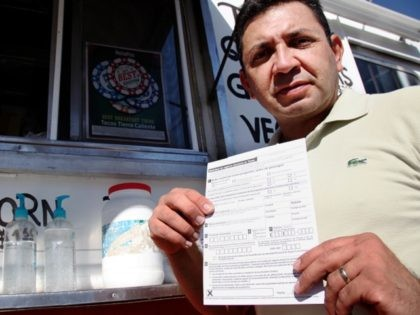 Carlos Zamora shows a voter registration card from a pile placed on the counter of the Tierra Caliente taco truck on Thursday, Sept. 29, 2016, in Houston. Zamora is with Mi Familia Vota, a Latino activist group that seeks to register more voters in the Latino community. Mi Familia Vota …