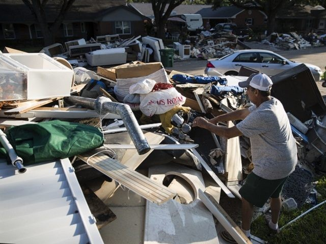 Steve Blatt helps a neighbor to retrieve an item from a debris pile in the aftermath of Hurricane Harvey on Wednesday, Sept. 6, 2017, in Houston. (AP Photo/Matt Rourke)