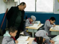 This photo taken on November 7, 2016 shows a teacher supervising students in the Yang Dezhi 'Red Army' elementary school in Wenshui, Xishui country in Guizhou province. In 2008, Yang Dezhi was designated a 'Red Army primary school' -- funded by China's 'red nobility' of revolution-era Communist commanders and their …