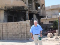 Former Rep. Frank Wolf (R-VA) stands in front of the ruins of a Christian community in Iraq in August 2017 (Photo courtesy Martha Hudson)