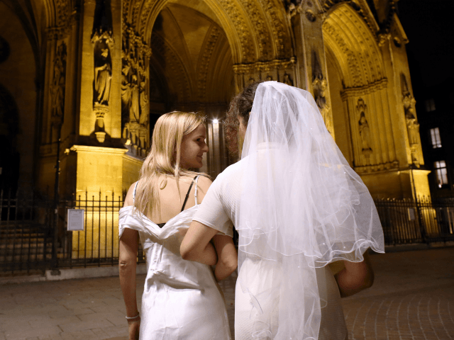 Members of the efFRONTe-e-s collective pose during a fake wedding as part of a gay-friendly and pro-secular happening, on October 30, 2012, in front of Sainte-Clothilde Basilic in Paris. AFP PHOTO /THOMAS SAMSON (Photo credit should read THOMAS SAMSON/AFP/Getty Images)