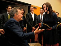 Former President George H.W. Bush, left, receives a tri-corner hat from actress Heather Lind, right, at a private screening of AMC's new series TURN on Saturday, March, 29, 2014 in Houston, Texas. (Photo by Aaron M. Sprecher/Invision for AMC/AP Images)