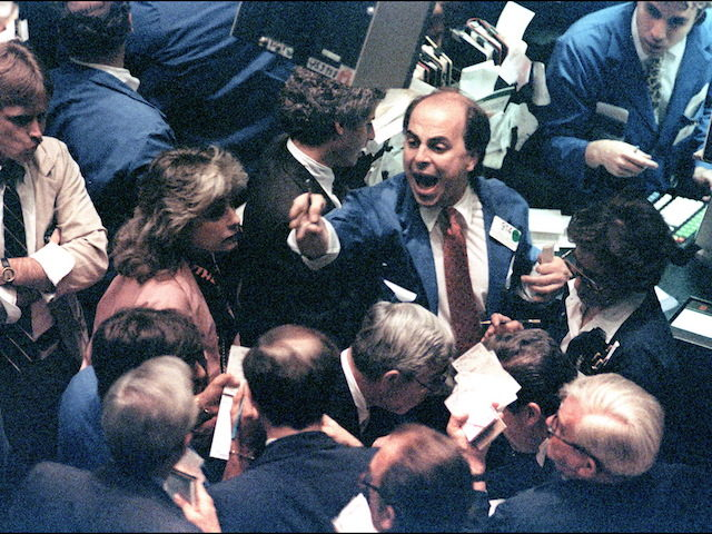 (FILES) A file photo dated 19 October, 1987 shows a trader (C) on the New York Stock Exchange shouting orders as stocks were devastated during one of the most frantic days in the exchange's history. The Dow Jones index plummeted 22.68 percent, some 508 points, to close at 1,738.41 points …