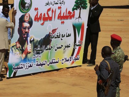 Sudanese security forces watch on as supporters of Sudan's President Omar al-Bashir (portrait) hold a banner as they gather for the incumbent president's campaign rally for the upcoming presidential elections in El-Fasher, in North Darfur, on April 8, 2015. Sudanese go to the polls on April 13 in legislative and …