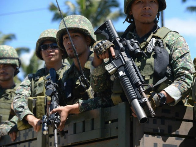Philippine troops ride on their truck on their way to the frontline in the outskirts of Marawi on the southern island of Mindanao on June 28, 2017. Islamist militants occupying parts of a southern Philippine city used a water route to bring in ammunition and evacuate wounded fighters, helping them …