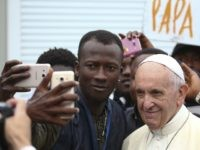 Pope Francis poses for a selfie with a man as he visits a migrant reception centre during a pastoral visit in Bologna, on October 1, 2017. / AFP PHOTO / POOL / ALESSANDRO BIANCHI (Photo credit should read ALESSANDRO BIANCHI/AFP/Getty Images)