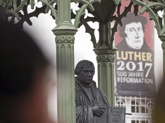 Visitors walk in front of the Martin Luther monument prior the celebrations on the occasion the 500th Anniversary of the Reformation in Wittenberg, Germany, Tuesday, Oct. 31, 2017. German will leaders mark the 500th anniversary of the day Martin Luther is said to have nailed his theses challenging the Catholic …