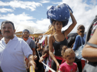 FILE - In this July 17, 2016 file photo, a woman carrying a bundle on her head waits in line to cross the border into Colombia through the Simon Bolivar International Bridge in San Antonio del Tachira, Venezuela. An estimated 25,000 Venezuelans trek across the international bridge into Colombia each …