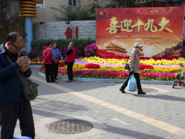 """In this Oct. 16, 2017 photo, residents pass by a board with the words """"Welcome the 19th Congress"""" on the streets of Beijing, China. Extraordinary security measures are being imposed ahead of the party congress, in addition to the typical security forces, thousands of deputized citizens patrol the streets, and …"""