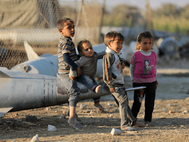 Syrian children play as they sit on the tip of an abandoned missile at the Ash'ari camp for the displaced in the rebel-held eastern Ghouta area outside the capital Damascus on October 25, 2017