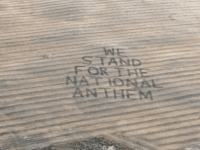 "Gene Hanson, Edgeley ND went from a Tribute to Prince and Political drawings in a farm field to a Patiotic sign ""WE STAND FOR THE NATIONAL ANTHEM"". This one measures about 2 football fields and took 2 hours to make. Was done with his tractor and disc. Used his plane …"