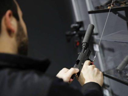 A visitors pulls the slide of a pistol with a silencer at a gun displays at a National Rifle Association outdoor sports trade show on February 10, 2017 in Harrisburg, Pennsylvania. / AFP / DOMINICK REUTER (Photo credit should read DOMINICK REUTER/AFP/Getty Images)