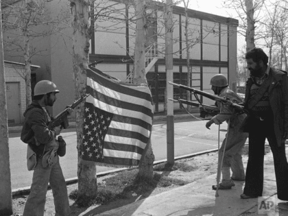 Iran rebels pose with a U.S. flag they bayoneted upside down on trees at Sultanabad Garrison northeast of Tehran, Iran on Feb. 12, 1979. (AP Photo/Saris)