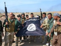 Iraqi Kurdish Peshmerga fighters pose for a photo holding an Islamic State (IS) group flag in the village of Sultan Mari west of the city of Kirkuk on March 9, 2015 after they reportedly re-took the area from IS jihadists. IS spearheaded a sweeping offensive in June 2014 that overran …