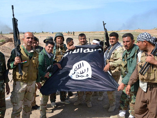 Iraqi Kurdish Peshmerga fighters pose for a photo holding an Islamic State (IS) group flag in the village of Sultan Mari west of the city of Kirkuk on March 9, 2015 after they reportedly re-took the area from IS jihadists. IS spearheaded a sweeping offensive in June 2014 that overran large parts of the country north and west of Baghdad, including in Kirkuk province. AFP PHOTO / MARWAN IBRAHIM (Photo credit should read MARWAN IBRAHIM/AFP/Getty Images)