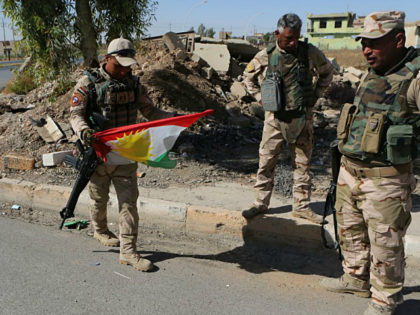 Iraqi soldiers remove a Kurdish flag from a checkpoint in Bashiqa, Iraq, Wednesday, Oct. 18, 2017. Iraqi forces took control of the mixed Yazidi-Christian town of Bashiqa on the northeastern outskirts of Mosul on Tuesday. Kurdish forces pulled out of disputed areas across northern and eastern Iraq a day after handing Kirkuk to federal forces amid a tense standoff following last month's vote for independence. (AP Photo/Khalid Mohammed)