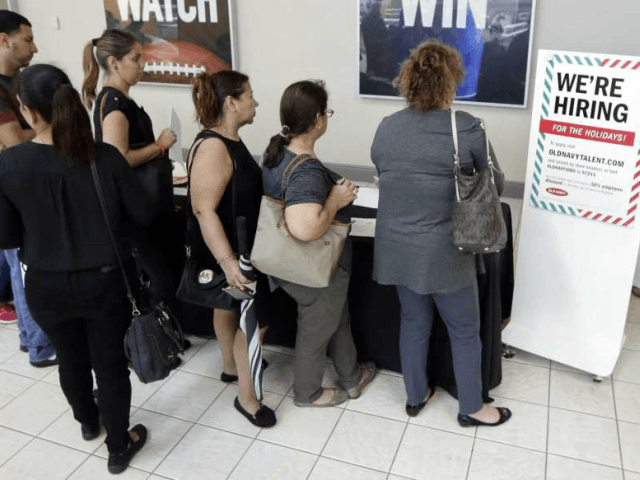 In this Tuesday, Oct. 3, 2017, photo, job seekers wait in line at a job fair at the Dolphin Mall in Sweetwater, Fla. The Labor Department said Thursday, Oct. 19, 2017, that claims for jobless aid dropped by 22,000 to 222,000, fewest since March 1973. (AP Photo/Alan Diaz)