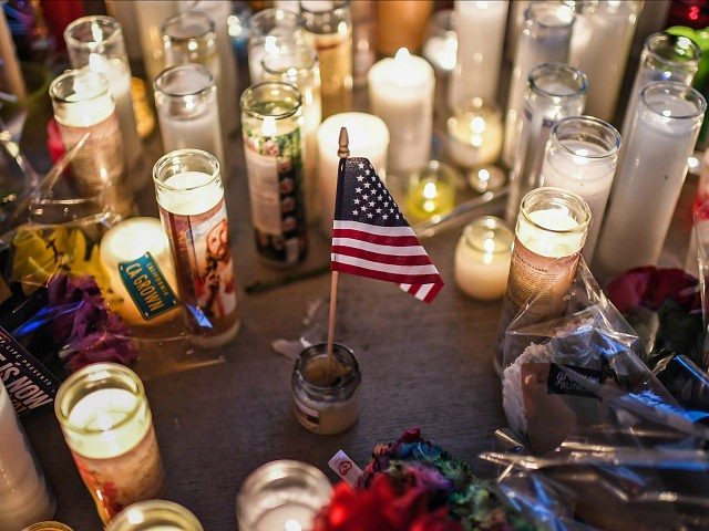 LAS VEGAS, NV - OCTOBER 3: A U.S. flag is placed in the middle of flowers and candles at a vigil that was held for the victims along the Las Vegas Strip a day after 59 people were killed and more than 500 wounded at the Route 91 Harvest Country Music Festival on Monday, October 2, 2017, in Las Vegas, NV. (Photo by Salwan Georges/The Washington Post via Getty Images)