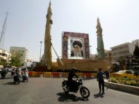 Iranians walk past Sejjil (L) and Qadr-H medium range ballistic missiles displayed next to a portrait of Iranian Supreme Leader Ayatollah Ali Khamenei on the occasion of the annual defence week which marks the anniversary of the 1980s Iran-Iraq war, on September 25, 2017, on Baharestan square in Tehran. / …