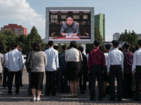 Spectators listen to a television news brodcast of a statment by North Korean leader Kim Jong-Un, before a public television screen outside the central railway station in Pyongyang on September 22, 2017