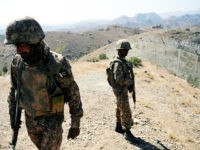 Pakistani soldiers patrol next to a newly fenced border fencing along Afghan border at Kitton Orchard Post in Pakistan's North Waziristan tribal agency on October 18, 2017. The Pakistan military vowed on October 18 a new border fence and hundreds of forts would help curb militancy, as it showcased efforts …