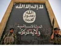 Fighters from the Hashed al-Shaabi (Popular Mobilisation units), backing the Iraqi forces, stand in front of a mural depicting the emblem of the Islamic State (IS) group as troops advance through Hawija on October 5, 2017, after retaking the city from Islamic State (IS) group fighters. Iraqi forces retook one …
