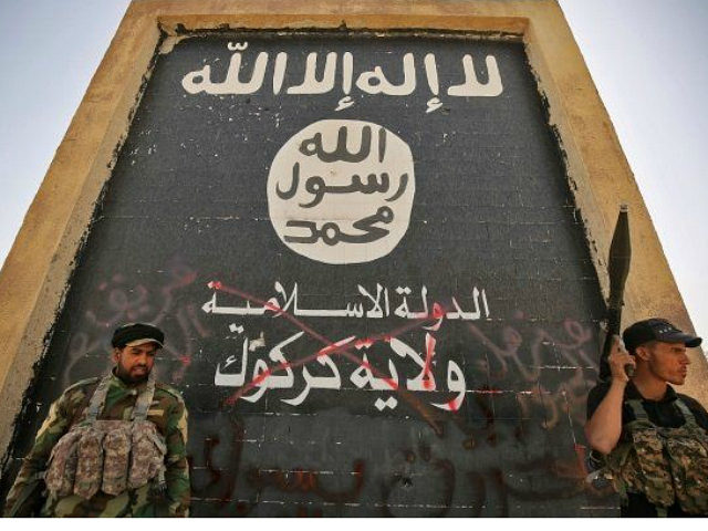 Fighters from the Hashed al-Shaabi (Popular Mobilisation units), backing the Iraqi forces, stand in front of a mural depicting the emblem of the Islamic State (IS) group as troops advance through Hawija on October 5, 2017, after retaking the city from Islamic State (IS) group fighters. Iraqi forces retook one of the Islamic State group's last two enclaves in the country on October 5, overrunning the longtime insurgent bastion of Hawija after a two-week offensive. / AFP PHOTO / AHMAD AL-RUBAYE (Photo credit should read AHMAD AL-RUBAYE/AFP/Getty Images)