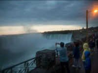 Tourists take photographs of the Horseshoe Falls in Niagara Falls, Ontario, Canada, on Wednesday, June 21, 2017. The 150th anniversary of Canada, promoted as Canada 150, marks the sesquicentennial anniversary of the Canadian Confederation and will be celebrated on nationally on July 1, 2017. Photographer: Brent Lewin/Bloomberg via Getty Images