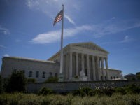 WASHINGTON, DC - JUNE 26: A flag flys outside the U.S. Supreme Court after it was announced that the court will allow a limited version of President Donald Trump's travel ban to take effect June 26, 2017 in Washington, DC. The Supreme Court will consider the case of the president's power on immigration in the fall but in the meantime agreed to allow a limited ban on travelers from six mostly Muslim countries to take effect. (Photo by Eric Thayer/Getty Images)
