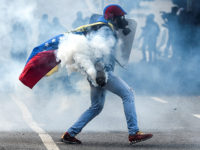 CARACAS, VENEZUELA, JULY 9: A protester with a tear gas mask and the Venezuelan flag holding a tear gas carister during clashes with the Bolivarian National Guard in a demonstration marking 100 days of protests against Venezuelan President Nicolas Maduro in Caracas, on July 9, 2017. Venezuela hit its 100th day of anti-government protests on Sunday, one day after its most prominent political prisoner, Leopoldo Lopez, vowed to continue his fight for freedom after being released from jail and placed under house arrest. At least 91 people have died since non-stop street protests began on April 1. (Photo by Carlos Becerra/Anadolu Agency/Getty Images)