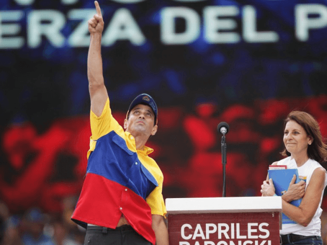 Opposition presidential candidate Henrique Capriles Radonski greets supporters with his mother, Monica Radonski, during a campaign rally in Caracas, Venezuela, on Sunday. Capriles is running against President Hugo Chavez in the country's Oct. 7 election. (photo credit: Rodrigo Abd/AP Photo)