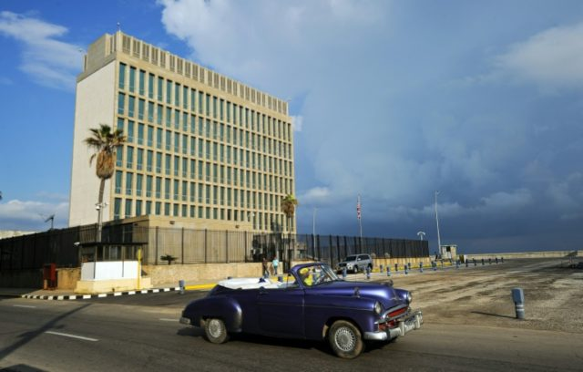A vintage car drives by the US Embassy in Havana the staff at which Secretary of State Rex Tillerson said would be reduced to a minimum