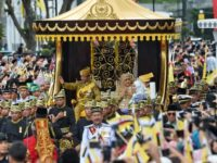 Brunei's Sultan Hassanal Bolkiah and Queen Saleha wave to crowds during Thursday's golden jubilee procession