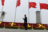 A man walks past decorations for the Communist Party's 19th Congress in Tiananmen Square, on the eve of its opening