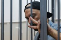 Russian theatre and film director Kirill Serebrennikov gestures from the defendants' cage in a Moscow court in August