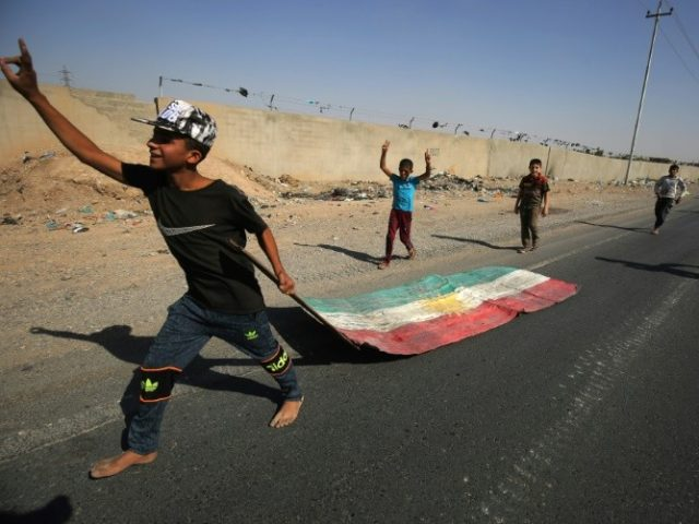 An Iraqi boy drags a Kurdish flag as Iraqi forces advance towards the centre of Kirkuk during an operation against Kurdish fighters on October 16, 2017.