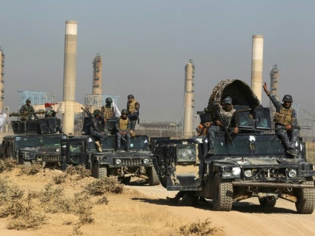 Iraqi forces pass an oil production plant as they advance towards the city of Kirkuk on October 16, 2017 in their campaign to retake the disputed province from the Kurds