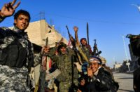 Members of the Syrian Democratic Forces celebrate at the frontline in the Islamic State (IS) group's crumbling stronghold of Raqa on October 16, 2017