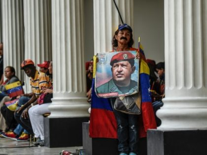 A supporter of Venezuelan President Nicolas Maduro holds a photo of his late predecessor Hugo Chavez, whose leftist ideology and government style continues to prevail in the South American country