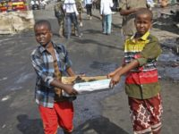 Somali children assist other civilians and security forces in their rescue efforts by carrying away unidentified charred human remains in a cardboard box, to clear the scene of Saturday's blast, in Mogadishu, Somalia, Sunday, Oct. 15, 2017. The death toll from the huge truck bomb blast in Somalia's capital rose …
