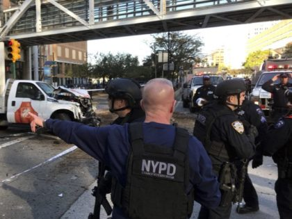 In this photo provided by the New York City Police Department, officers respond to a report of gunfire along West Street near the pedestrian bridge at Stuyvesant High School in lower Manhattan in New York, Tuesday, Oct. 31, 2017. (Martin Speechley/NYPD via AP)