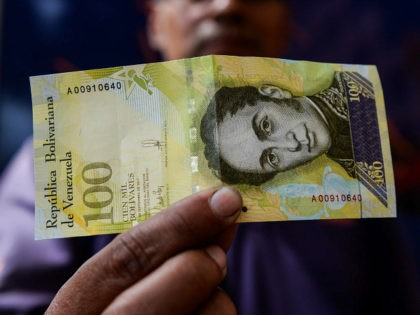 A man shows a new one hundred thousand-Bolivar-note in Caracas on November 9, 2017. The new bill is worth 29,89 US dollars in the official market and 2 dollars in the black market at November 9, 2017 exchange rate. / AFP PHOTO / FEDERICO PARRA (Photo credit should read FEDERICO …