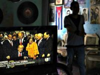 A television set shows President Donald Trump signing the new Cuba policy in a living room festooned with images of Cuban leade