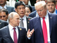 """U.S. President Donald Trump, right, and Russia's President Vladimir Putin talk during the family photo session at the APEC Summit in Danang, Saturday, Nov. 11, 2017. President Trump stood before a summit of Asian leaders keen on regional trade pacts and delivered a roaring """"America first"""" message Friday, denouncing China …"""