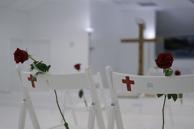 A memorial for the victims of the shooting at Sutherland Springs Baptist Church includes 26 white chairs, each painted with a cross and and rose, placed in the sanctuary, Sunday, Nov. 12, 2017, in Sutherland Springs, Texas. A man opened fire inside the church in the small South Texas community last week, killing more than two dozen. (AP Photo/Eric Gay)